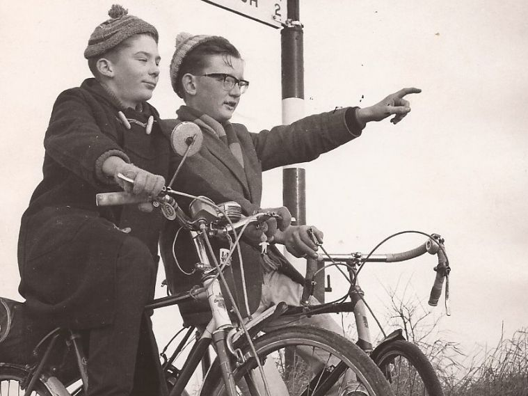 A black and white photo of two boys on bikes. One boy is pointing to the distance.
