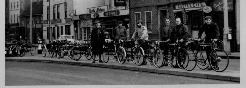 A black and white photo of a group of cyclists stood in front of some shops.