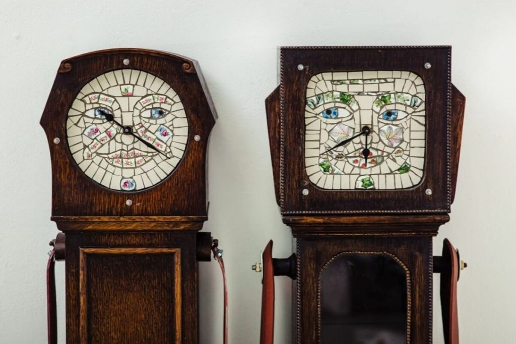 Two sculptures. Each has a clockface made out of a stained glass window.