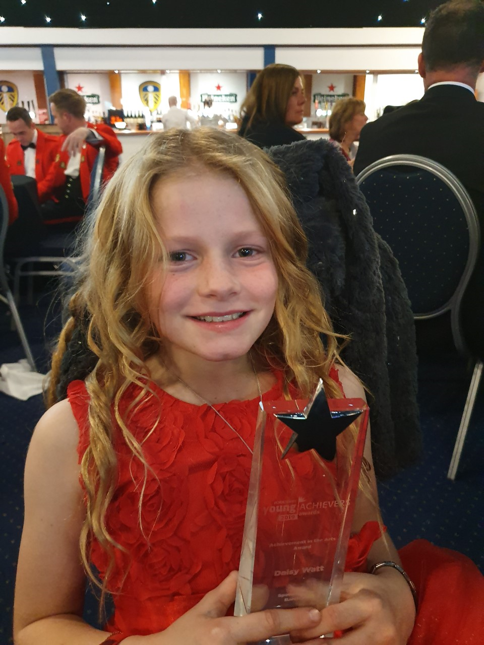 A girl holding a trophy with a star on it.